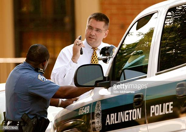 An unidentified congressional staff member and an Arlington County police officer talk outside the home of US Rep Paul Gillmor September 5 2007 in...