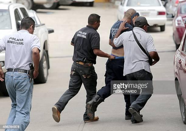 An unidentified detained police officer is escorted to testify in Acapulco Guerrero state Mexico on September 28 in regards to clashes with...