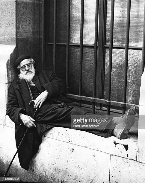 An unidentified elderly man in a beret sleeps on the ledge of a barred window a cane in his hands Paris France 1936