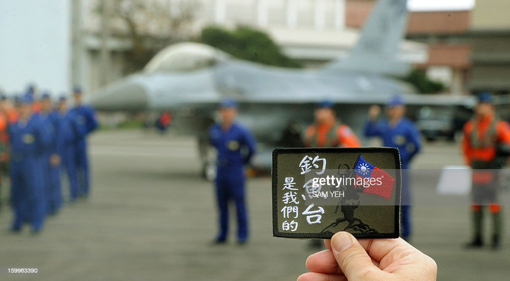 An unidentified employee displays a badge reading 'Diaoyu islands belonged us (Taiwan)' in front of a US-made F-16 fighter jet and pilots during the annual demonstration at the Hualien air force base on January 23, 2013. A boat carrying Taiwanese activists headed for disputed Japanese-controlled islands turned back after coastguard vessels from the two sides converged and duelled with water cannon. AFP PHOTO / Sam Yeh