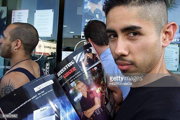 An unidentified fan shows off a signed copy of Playboy Magazine's July 2001 issue featuring Los Angeles Police Department Patrol Officer Ginger...