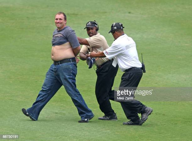 An unidentified fan trespasses on the field while Turner Field security guards contain and arrest him during the ninth inning of the game between the...