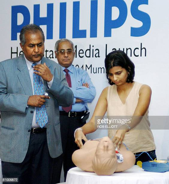 An unidentified female member of the Indian press to show the symplicity of using the device applies patches to a dummy's chest during a...