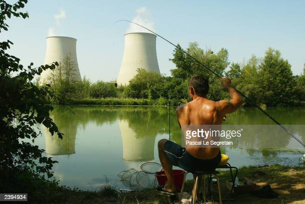 An unidentified fisherman casts his rod in the Seine river in front of nuclear station of NogentsurSeine on August 12 outside Paris France Soaring...