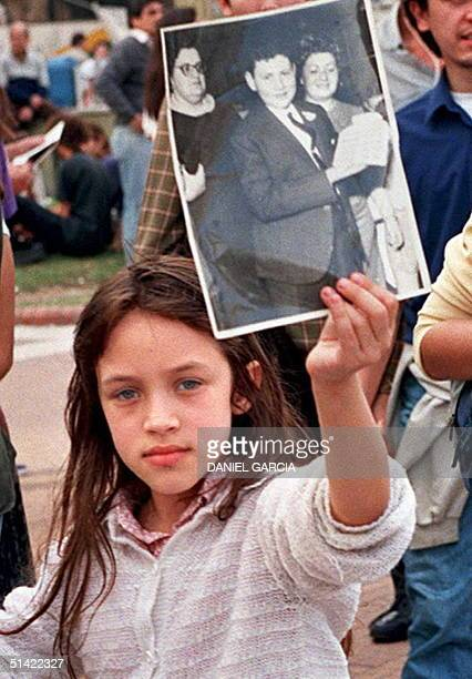 An unidentified girl carries the portrait of relatives who disappeared during the military regime of 19761983 at a rally organized by the Mothers of...