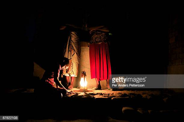 An unidentified girl listens as her mother and a friend chat after sunset on November 14 2005 in Galufu Malawi The village has seen an increase in...