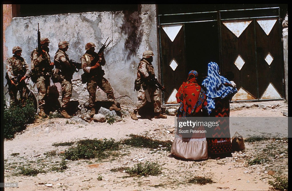 An unidentified group of US soldiers patrol a building January 11 1993 in Mogadishu Somalia The United Nations hopes to restore order and save...