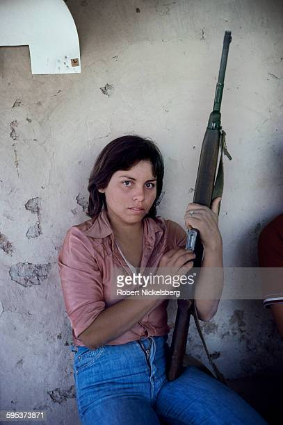 Portrait of an unidentified Fuerzas Populares de Liberacion guerrilla as she sits against a wall a rifle in her hands Chalatenango Province El...