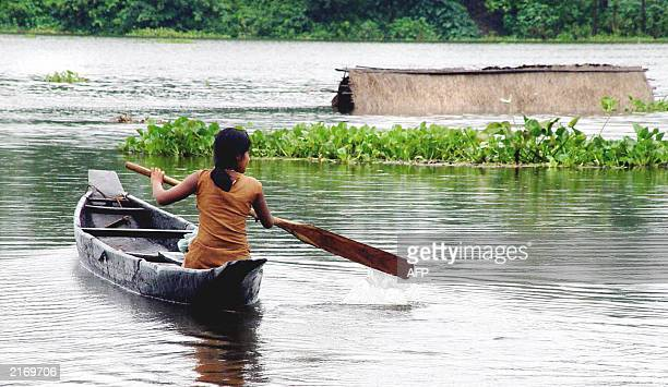 An unidentified Indian girl paddles a canoe past a partially submerged house at Panikhati some 20kms east of Guwahati 29 June 2003 Some 60 people...