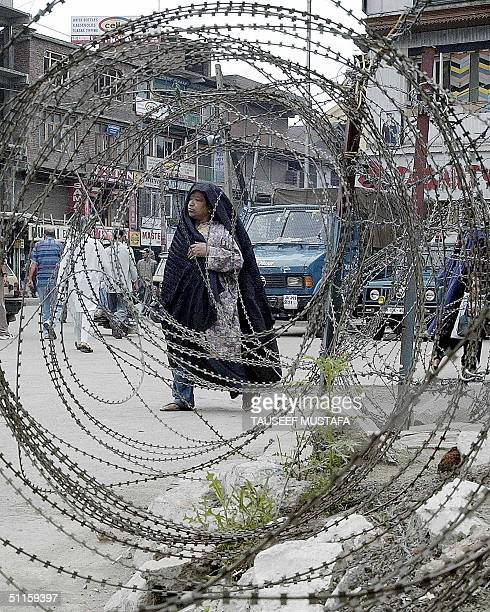 An unidentified Indian Kashmiri woman walks by a barbedwire fence during a stop and search operations in Srinagar's main commercial hub Lal Chowk 11...
