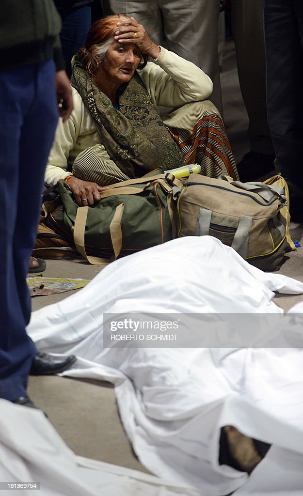 An unidentified Indian woman grieves as she sits next to the body of a dead relative at the railway station in Allahabad on February 10, 2013. At least 10 people died in the stampede as pilgrims headed home from India's giant Kumbh Mela festival, which drew a record 30 million people to the banks of the river Ganges. Dozens more were injured in the crush and some local television channels put the death toll as high as 20. Local officials said that the railings on a bridge at Allahabad station had given way under the pressure of the mass of people, while eyewitnesses told local media that the police had baton-charged the crowd leading to panic.
