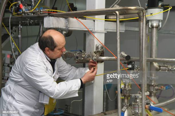 An unidentified International Atomic Energy Agency inspector disconnects the connections between the twin cascades for 20 percent uranium production...