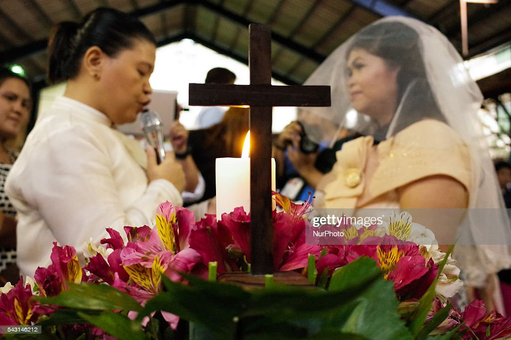 "An unidentified LGBT couple exchange vows during a mass wedding ceremony at Barangay Sangandaan in Quezon City on Sunday, 26 June 2016. The LGBT Christian Church, a small Christian ecumenical group, performed its own ""wedding rites"" for eight couples at a basketball court on Sunday, although same-sex unions are not legally recognized and rejected by the dominant Roman Catholic church in the country."