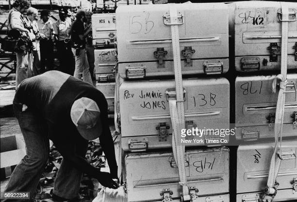 An unidentified man a strap onto a stack of aluminum coffins for shipment to the United States following the more than 900 deaths in the mass suicide...