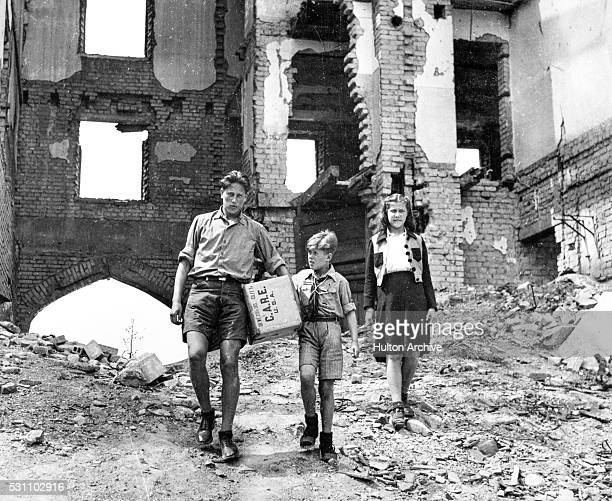 An unidentified man along with boy and girl walk over the rubble in the shell of a building with a CARE package 1940s or 1950s CARE was a...