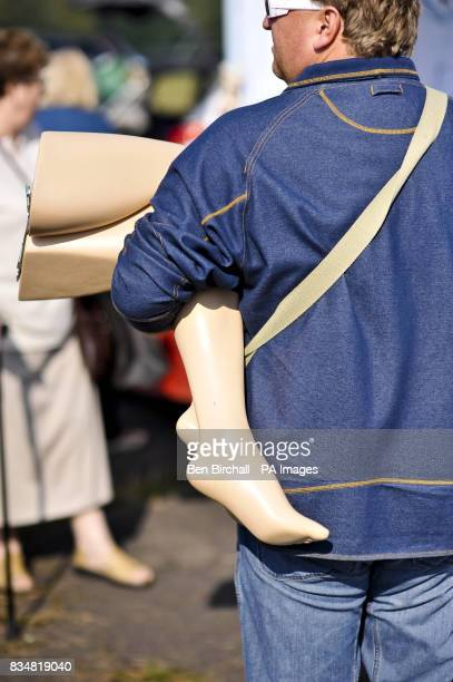 An unidentified man carries items including a set of mannequin legs at a car boot sale at Manor Farm Chedworth Gloucestershire