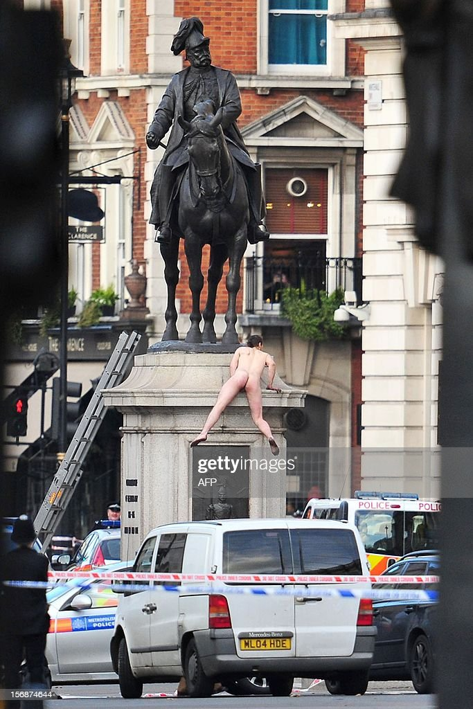 An unidentified man climbs down after standing naked on top of the statue of Prince George, Duke of Cambridge outside the Ministry of Defence building in Whitehall in central London on November 23, 2012. The man, who brought Whitehall to a standstill for almost two hours, stood naked on the statue and struck various poses before being eventually talked down. AFP PHOTO / JUSTIN TALLIS