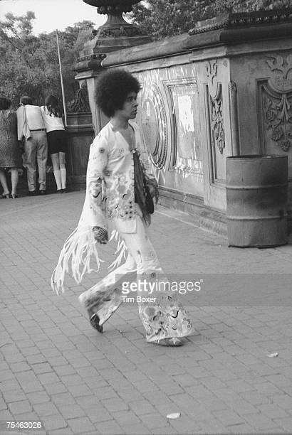 An unidentified man dressed in a fringed flowerprint suit with wide bellbottom trousers walks past an ornate concrete wall 1970