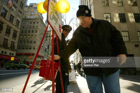 An unidentified man gives a donation to a holiday bell ringer from the Salvation Army November 25 2003 in New York City The US economy surged ahead...