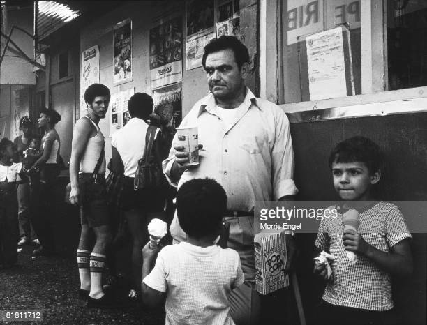 An unidentified man holds a box of popcorn in one hand and a Nathan's Famous cup in the other while he stands with two young boys both of whom eat...