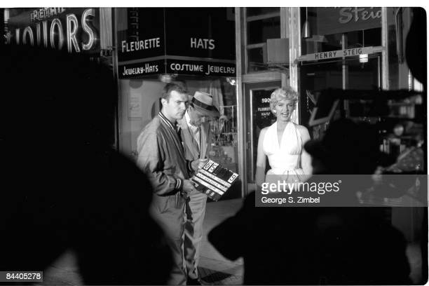 An unidentified man holds a clapboard as behind him American film actors Tom Ewell and Marilyn Monroe wait for filming to begin on location during...