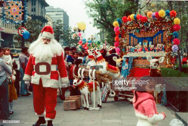 An unidentified man in a Santa Claus costume stands on the sidewalk while a crowd looks on at his modified sleigh Mexico City Mexico 2004