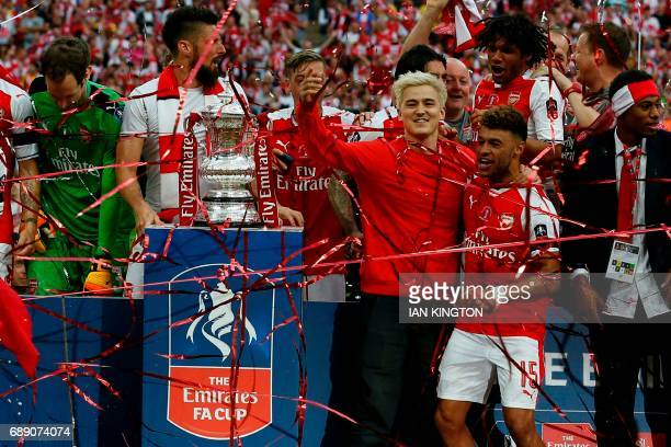 An unidentified man joins the players on the pitch as they celebrate after the English FA Cup final football match between Arsenal and Chelsea at...