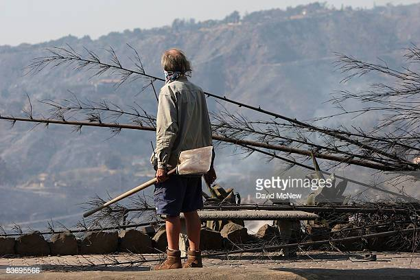 An unidentified man looks at his burned property after the Tea Fire swept through on November 14 2008 in Montecito California More than 100 homes...