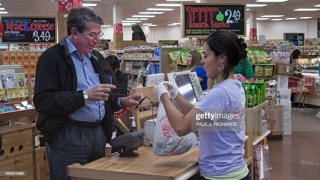 An unidentified man (L) pays for groceries at Trader Joe's in Centreville, Virginia, on September 13, 2013. The national supermarket chain informed part-time employees that it would end health insurance benefits in 2014 for employees who work less than 30 hours a week, sending them instead to the new public insurance marketplaces with an extra 500 USD to help purchase coverage. Under the Affordable Care Act (ACA), or 'Obamacare', companies are not required to offer health coverage to their part-time workers. AFP PHOTO/Paul J. Richards