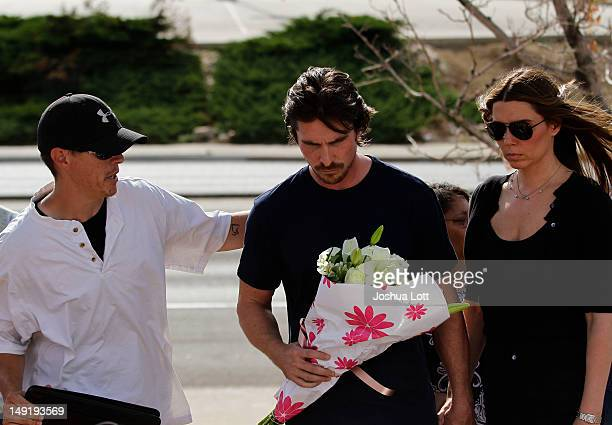 An unidentified man places his hand on actor Christian Bale's back as he holds flowers before placing them at the memorial across the street from the...