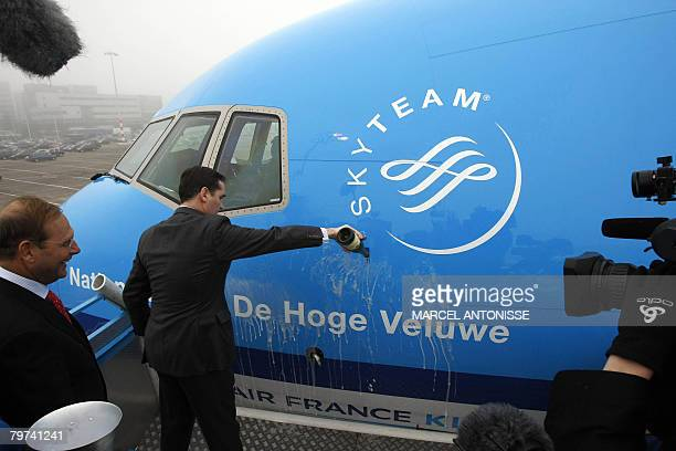 An unidentified man pours champagne KLM's first Boeing 777300 at Schiphol airport in Amsterdam 13 February 2008 The first two KLM Boeing airplanes...