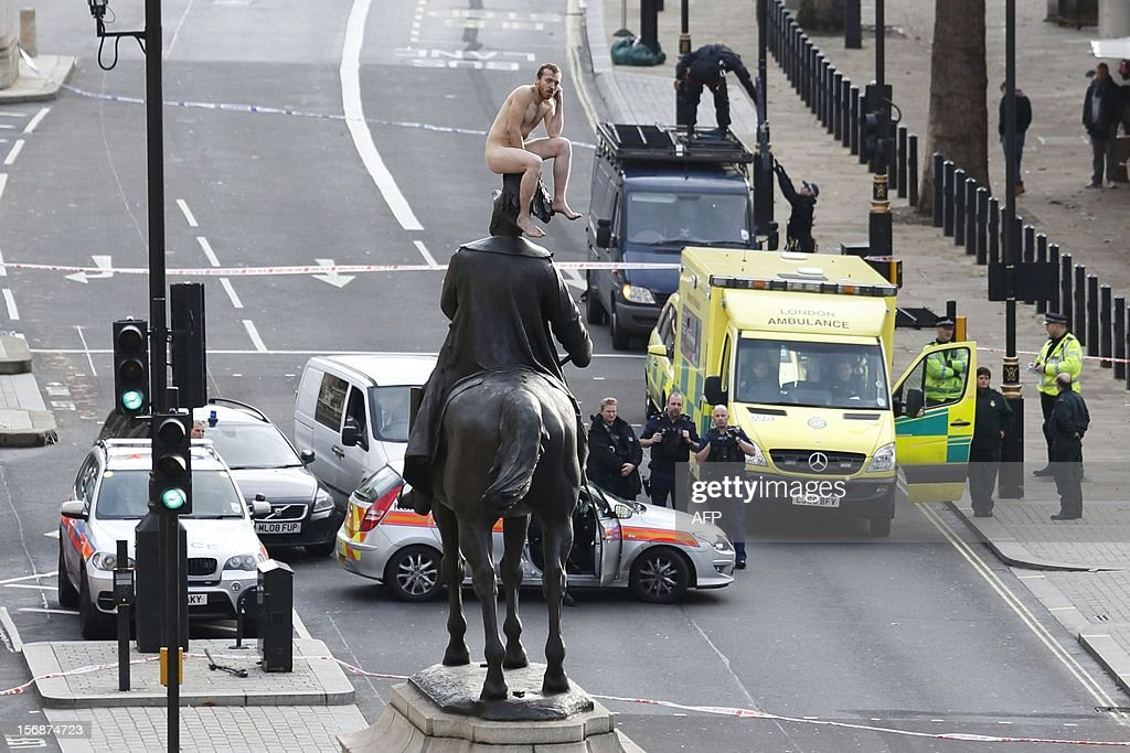 An unidentified man sits naked on top of the statue of Prince George, Duke of Cambridge outside the Ministry of Defence building in Whitehall in central London on November 23, 2012. The man, who brought Whitehall to a standstill for almost two hours, stood naked on the statue and struck various poses before being eventually talked down.