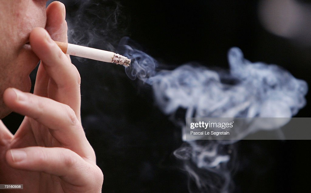 An unidentified man smokes a cigarette in the street outside his office on January 31, 2007 in Paris, France. France introduces a smoking ban in public places from February 1, 2007. Bars, restaurants, hotels and night clubs will follow from January 1, 2008.
