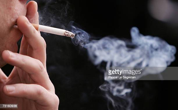 An unidentified man smokes a cigarette in the street outside his office on January 31 2007 in Paris France France introduces a smoking ban in public...