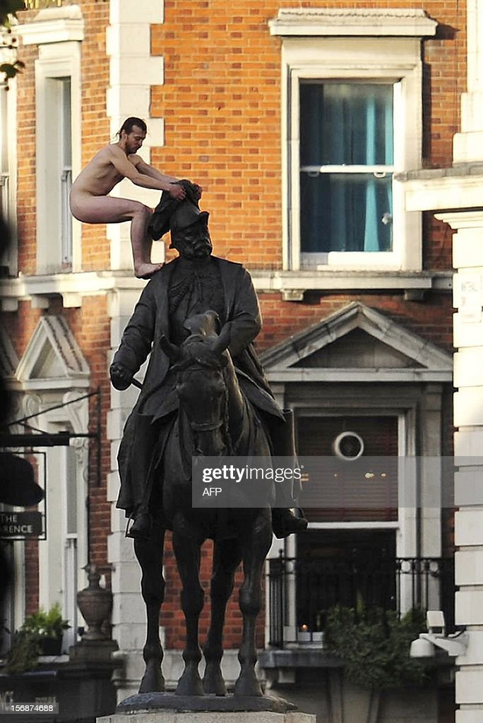 An unidentified man stands naked on top of the statue of Prince George, Duke of Cambridge outside the Ministry of Defence building in Whitehall in central London on November 23, 2012. A naked man brought parts of central London to a standstill after he installed himself on a statue near Prime Minister David Cameron's office for nearly three hours. He braved the November cold and gawking crowds to straddle the monument to Prince George, a 19th century military chief and one-time Duke of Cambridge, adopting various poses including balancing precariously on the prince's head.