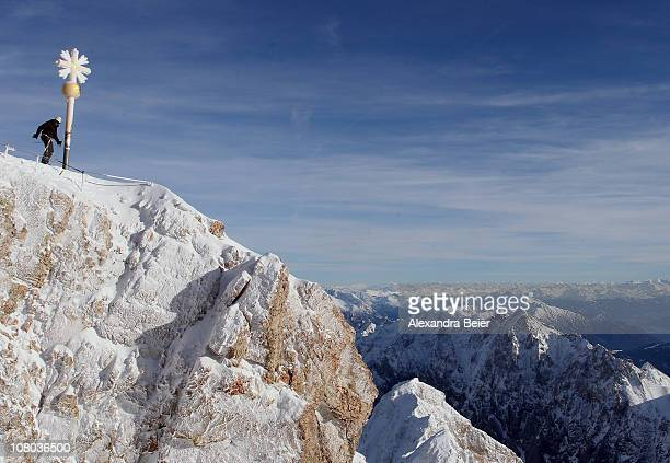 An unidentified man stands next to the summit cross of Germany's highest mountain Zugspitze on January 14 2011 near GarmischPartenkirchen Germany...
