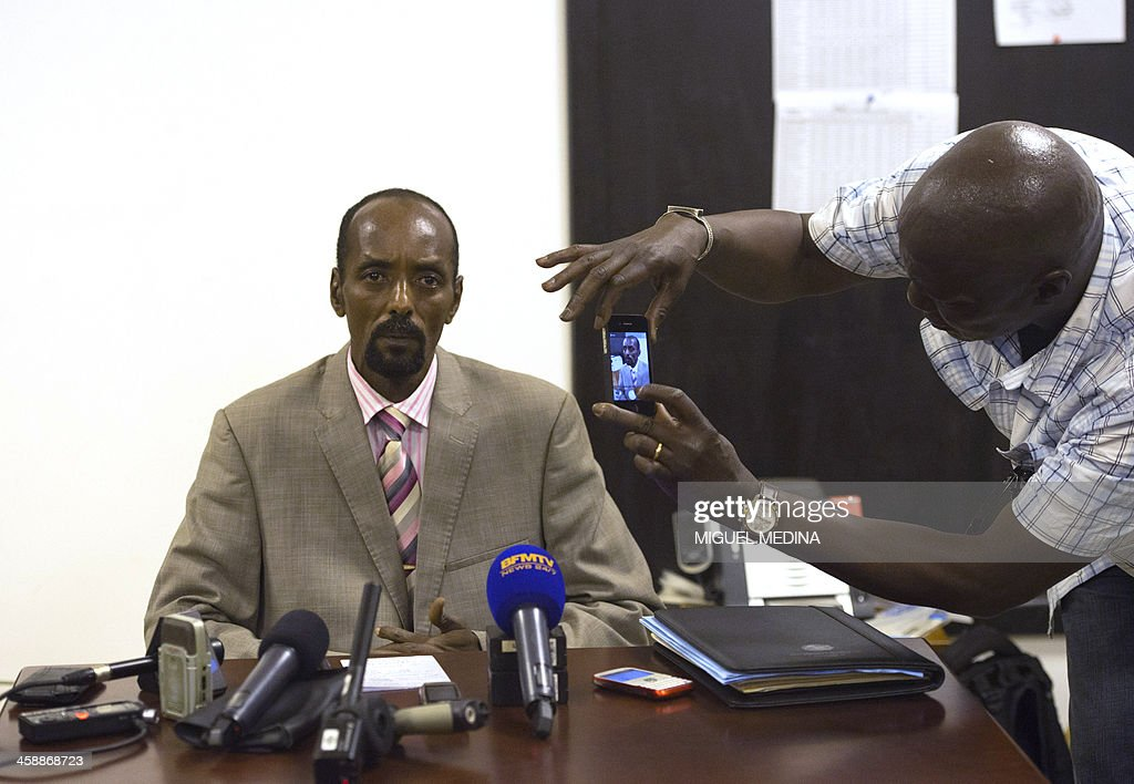 An unidentified man takes pictures with his mobile phone as Abakar Sabone, former leader of the Movement of the Central African Liberators for Justice (MLCJ), prepares to give a press conference in Bangui on December 22, 2013. Several thousand Muslims backing former Seleka rebels protested in the Central African Republic's capital on Sunday against French soldiers conducting a disarmament operation, AFP journalists in the city witnessed. The demonstration swelled after some Muslim residents said three ex-Seleka fighters were killed in clashes with French troops. French officials have not confirmed that information. AFP PHOTO/MIGUEL MEDINA