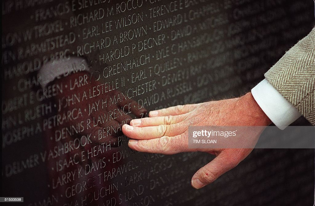 An unidentified man touches a name on the Vietnam memorial Wall in 11 November, 1999 in Washington, DC. US Veterans have traveled to Washington to visit the Wall in observance of Veteran's Day. AFP PHOTO/ Tim SLOAN