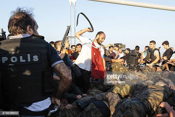 An unidentified man uses his belt to hit Turkish soldiers involved in the coup attempt that have now surrendered on Bosphorus bridge on July 16 2016...