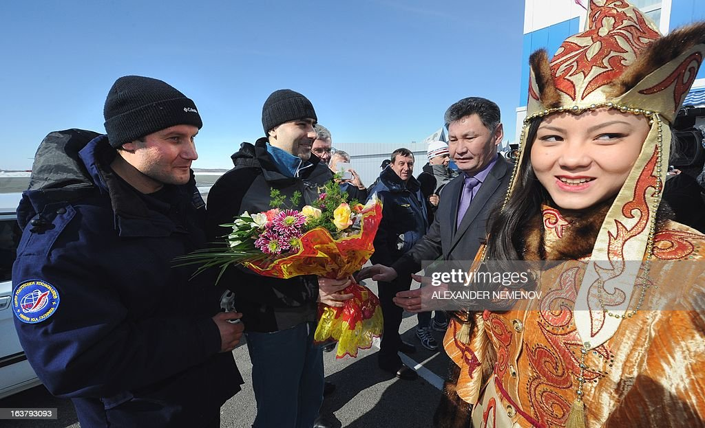 An unidentified man (L) watches as officials present flowers to Russian Flight Engineer Evgeny Tarelkin (2nd L) at the airport of Kostanay after their landing in northern Kazakhstan, on March 16, 2013. NASA US astronaut Kevin Ford together with Russian cosmonauts Oleg Novitskiy and Evgeny Tarelkin returned safely to Earth from the International Space Station early today, aboard a Russian capsule which landed on the freezing Kazakhstan steppe, mission control said.The landing had been delayed by a day due to poor weather conditions, but rescue helicopters still had to contend with thick ground fog which descended on the landing area and drastically reduced visibility.