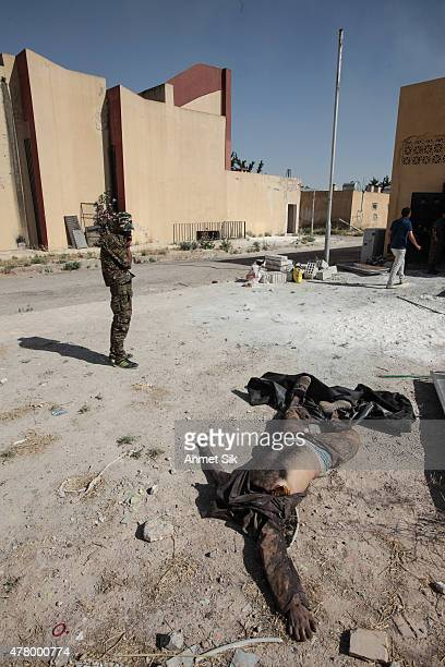 An unidentified man's dead body lies on a street as Kurdish People's Protection Units or YPG fighter controls the area in downtown of Tal Abyad Syria...
