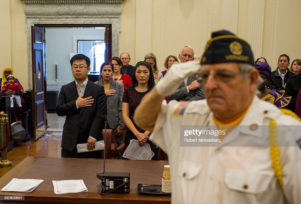 An unidentified member of the Honor Guard of the American Legion salutes as the National Anthem is played during a naturalization ceremony for 25...