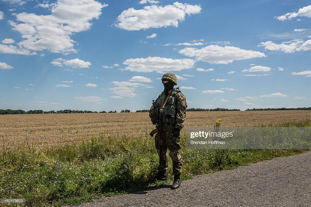 An unidentified member of the security detail for inspectors from the Organization for Security and Cooperation in Europe (OSCE) and the Dutch government stands watch at the Malaysia Airlines flight MH17 crash site during the inspectors' visit on July 21, 2014 in Grabovo, Ukraine. Malaysia Airlines flight MH17 was travelling from Amsterdam to Kuala Lumpur when it crashed killing all 298 on board including 80 children. The aircraft was allegedly shot down by a missile and investigations continue over the perpetrators of the attack.