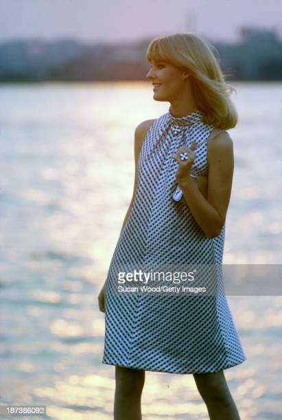 An unidentified model in a black and white sleeveless halterneck dress and with a silver clutch poses beside the water at sunset Malibu California...