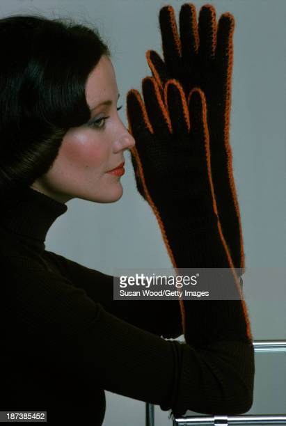 An unidentified model in a brown turtleneck sweater and elbowlength handknitted gloves with red trim February 1975 The photo was taken as part of a...