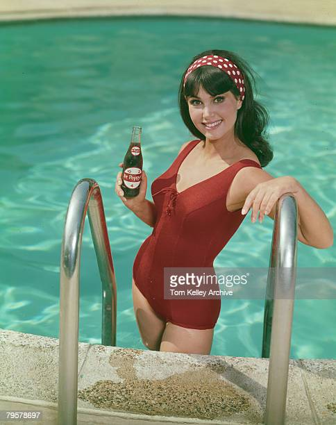 An unidentified model in a red swimsuit and headband smiles as she poses on a swimming pool ladder with bottle of Dr Pepper soda in one hand June...