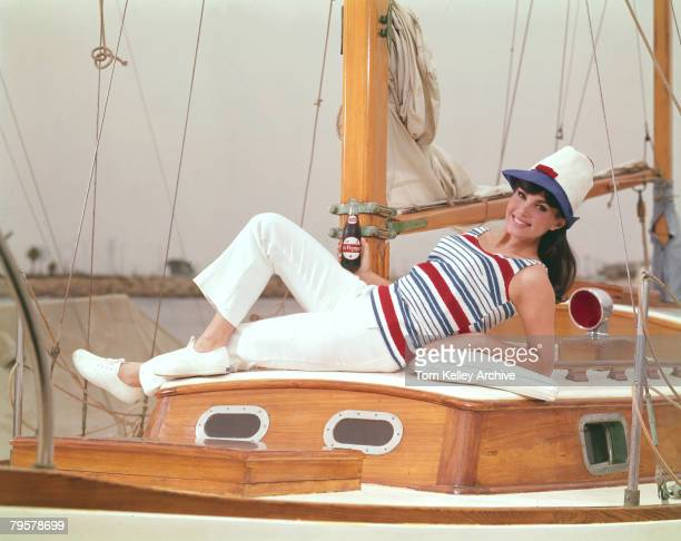 An unidentified model in a striped top and tall cap smiles as she reclines on a sailboat with bottle of Dr Pepper soda in one hand June 1965 The...