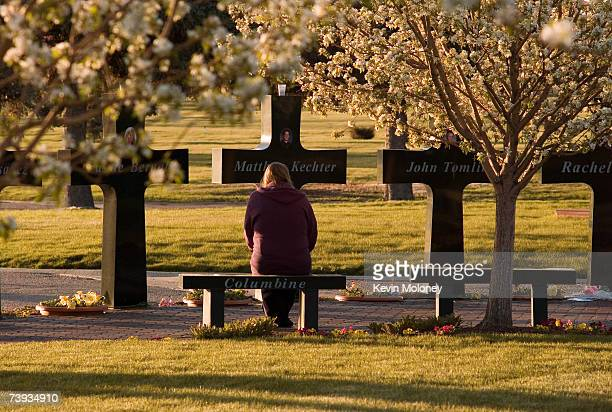 An unidentified mourner pauses at a memorial that stands around the graves of three of the Columbine High School shooting victims at Chapel Hill...