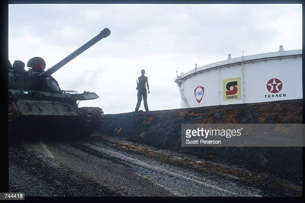 An unidentified MPLA soldier patrols American oil storage tanks and facilities March 13 1993 in Soyo Angola State radio claims that government troops...