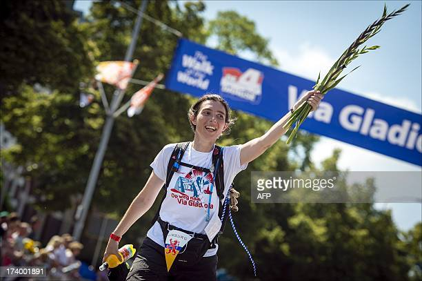 An unidentified participant with 'Limburg flag' on her belt celebrates with flowers after the finish line on July 19 2013 of the fourth and final day...